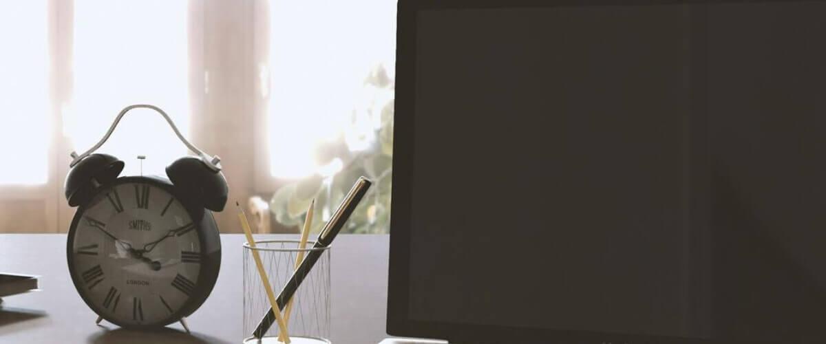 horloge avec ordinateur portable sur le bureau